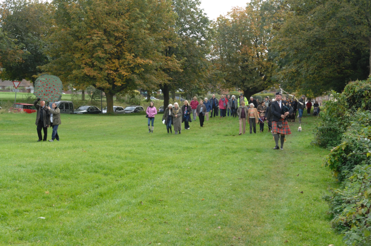 Piper Major Neil Moore of Marlborough College leads the way to the new Community Orchard
