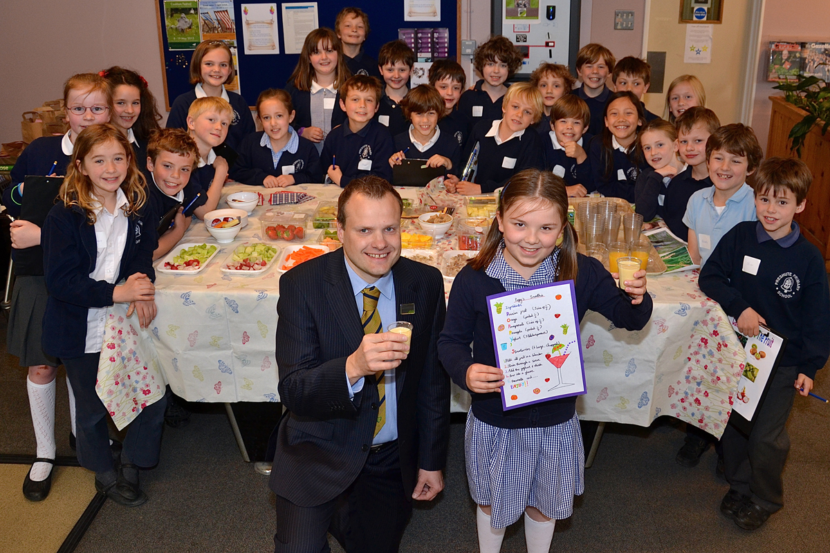 Waitrose store manager Ian Smith with Poppy Childs and children from Preshute School