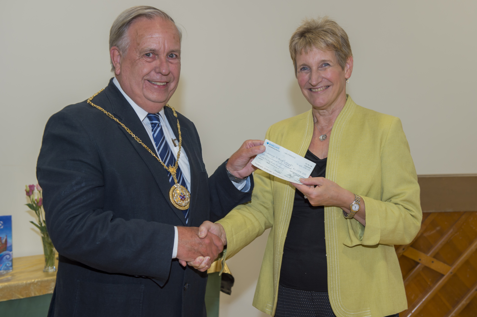 Mayor Mervyn Hall hands over the grant cheque for £2,244 to Head Teacher Anne Schwodler to support the purchase of 'C Touch' board and mount for the Key Stage 2 Complex Needs Resource Base
