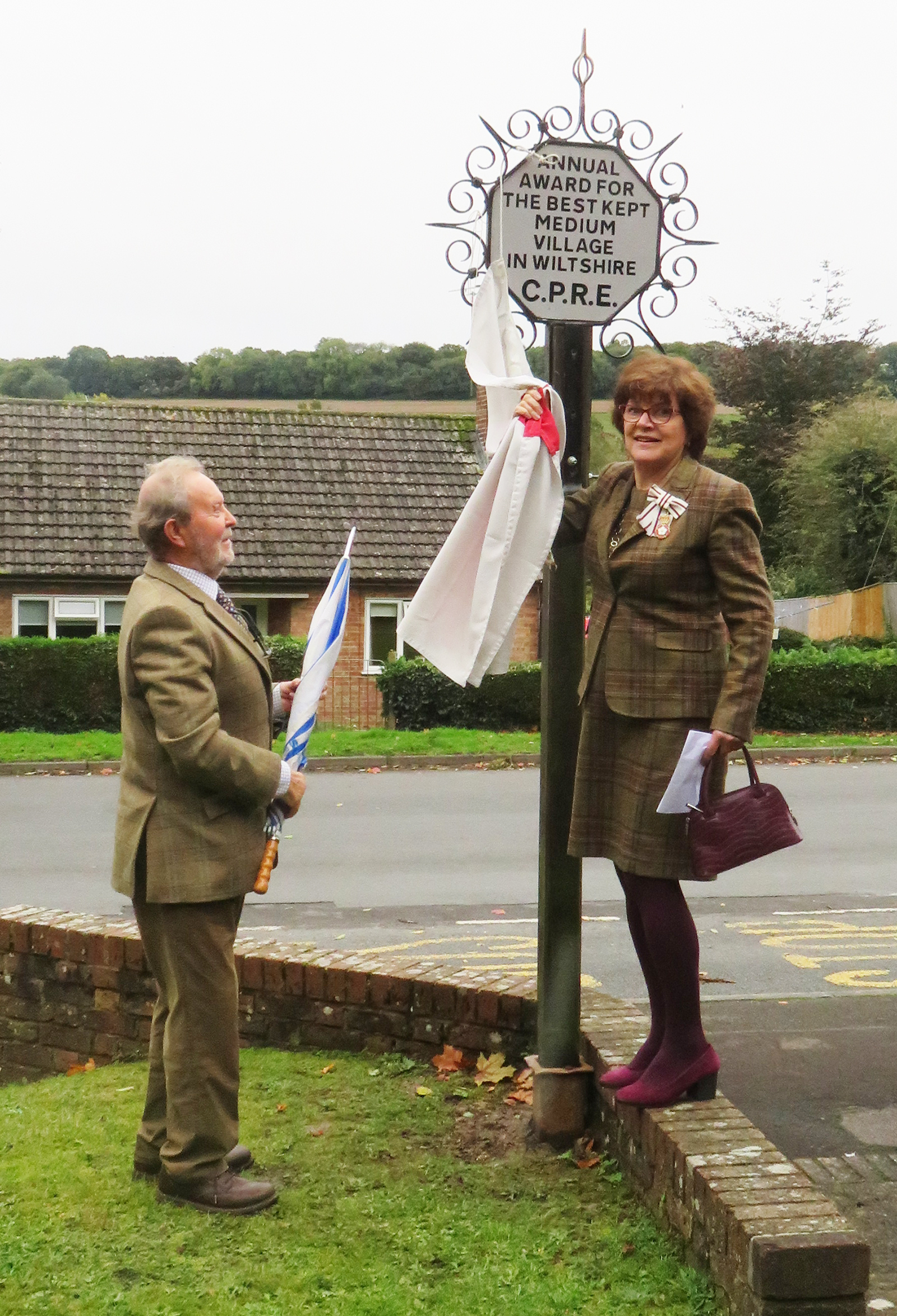 Mrs Sarah Troughton President of the Wiltshire Branch CPRE and Lord Lieutenant for Wiltshire unveils the standard and shield assisted by Sir Nigel Thompson Chair of Minal Parish Council