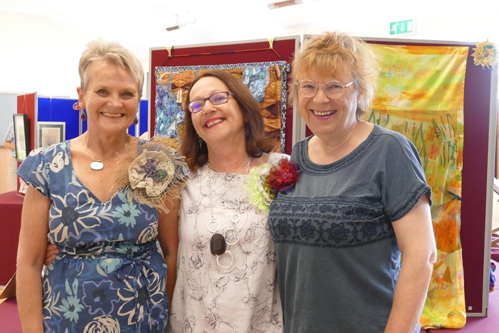 Left to right:  Ros Lomas Ann Smith Clare Russell in front of Ros and Ann's textile art