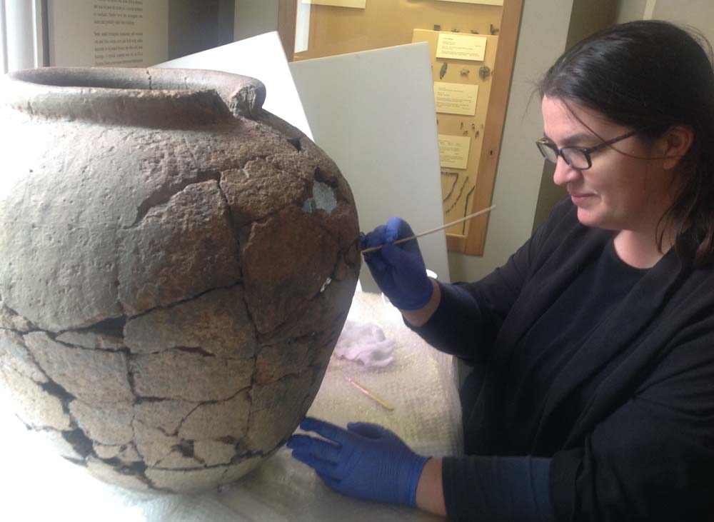 Pieta Greaves conserving the jar (Photo: Wiltshire Museum)