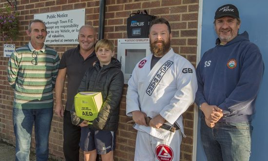 Kevin Palmer of the Gracie Brazilian Jiu Jitsu Martial Arts and Self Defence School declares the new Difbrillator open for use, supported by (l-r) Marlborough Town Chair Wally Ash, MYFC coach Keith Marshall, MYFC U14 Colts player Will Slater and MYFC Chair Stuart Slater