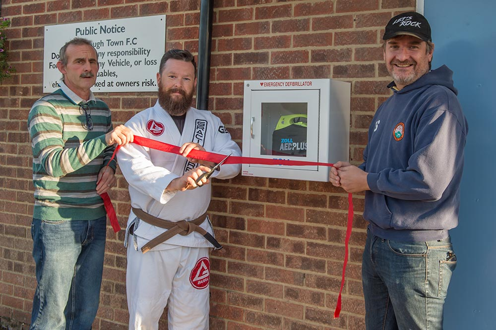 Kevin Palmer, owner of the Gracie Barra Brazilian Jiu Jitsu Martial Arts and Self Defence school cuts the tape to declare teh new Defibrillator open for use, flanked by Wally Ash, chair of MTFC (left) and Stuart Slater, chair of MYFC