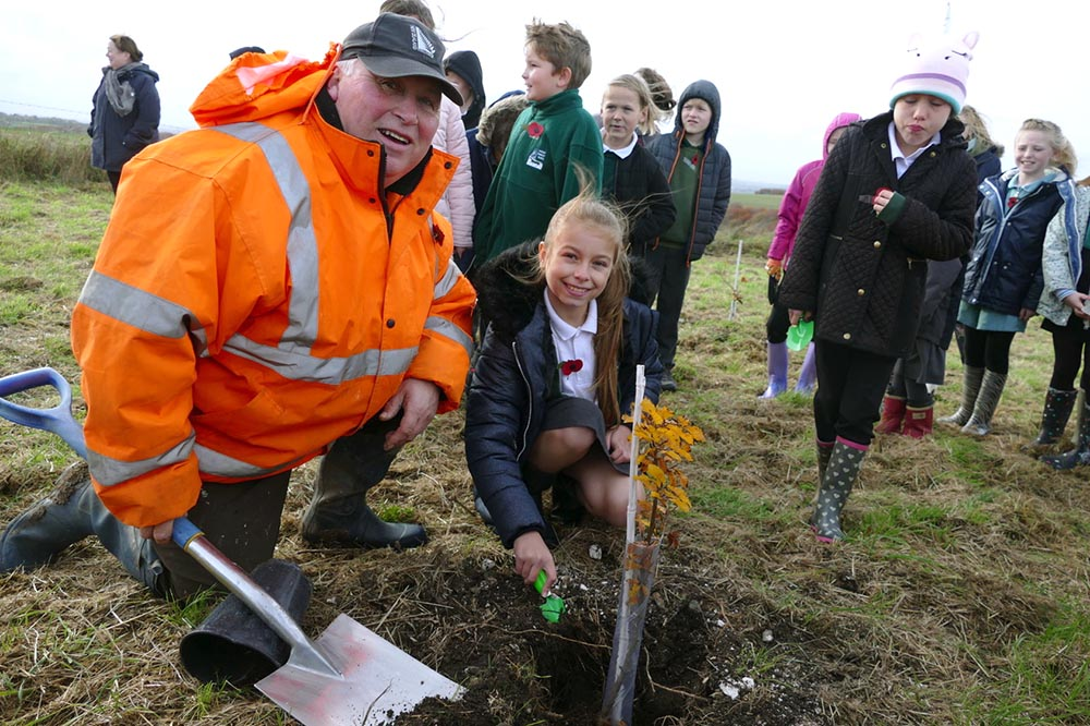 Councillor Phil Stevens assists a Pewsey Primary pupil to plant a beech tree