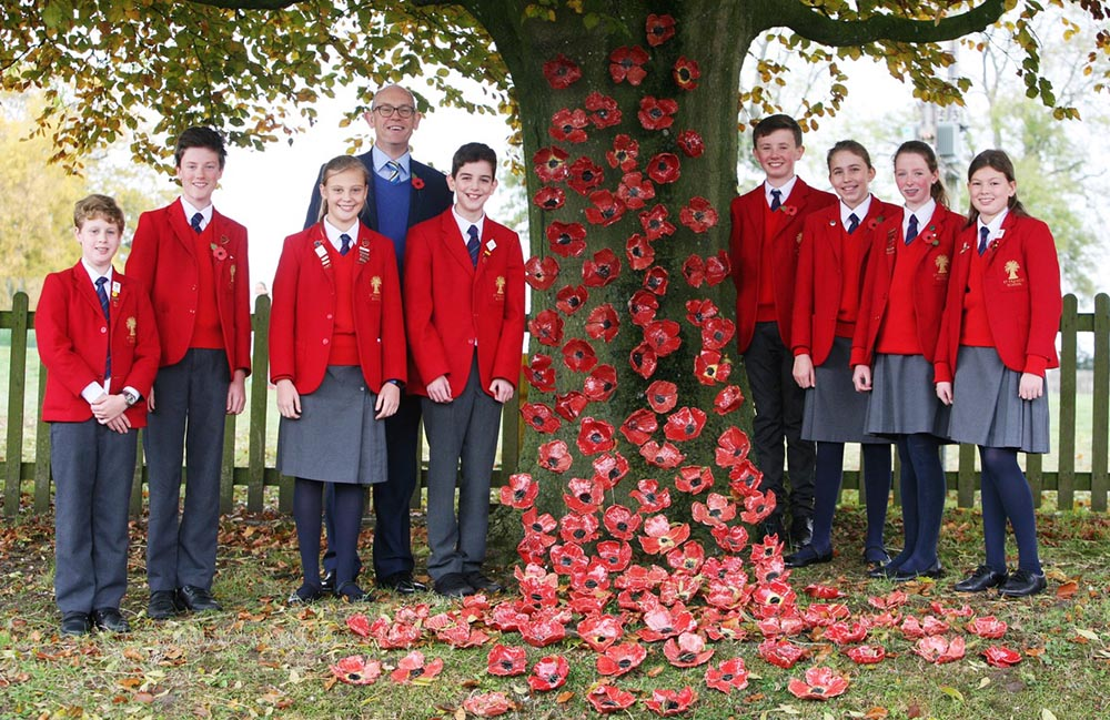 Headmaster David Sibson with St Francis pupils and the ceramic poppies they made