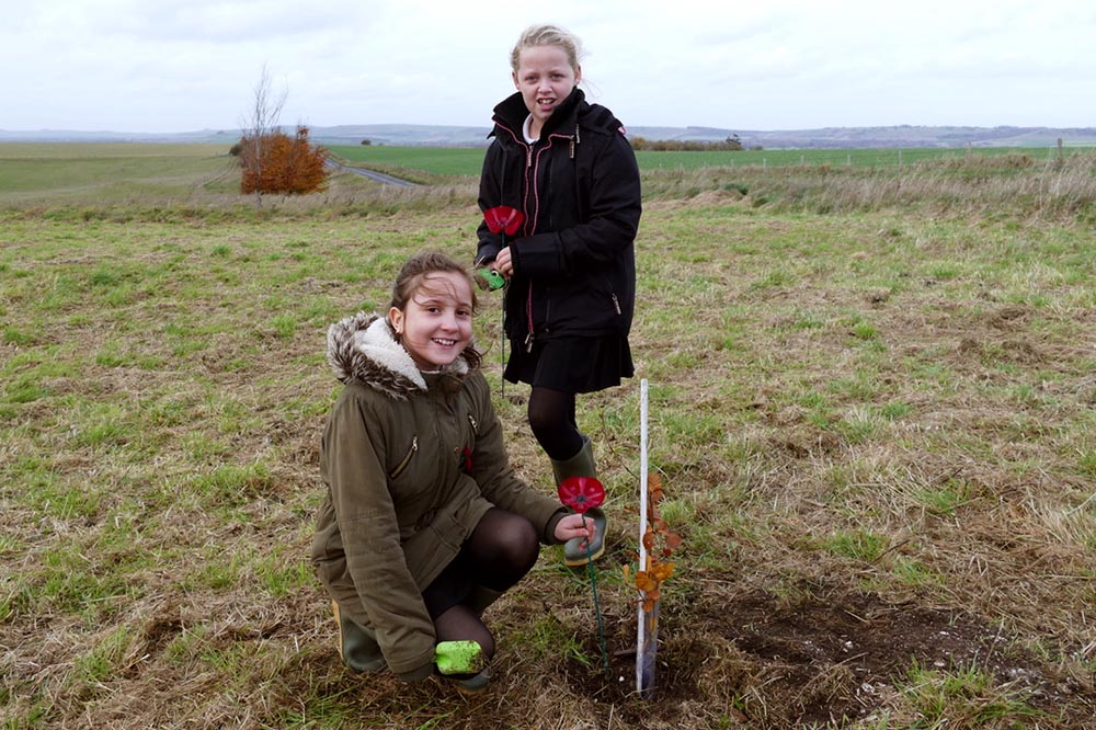 Two Pewsey Primary pupils plant the tree and add the poppy they made