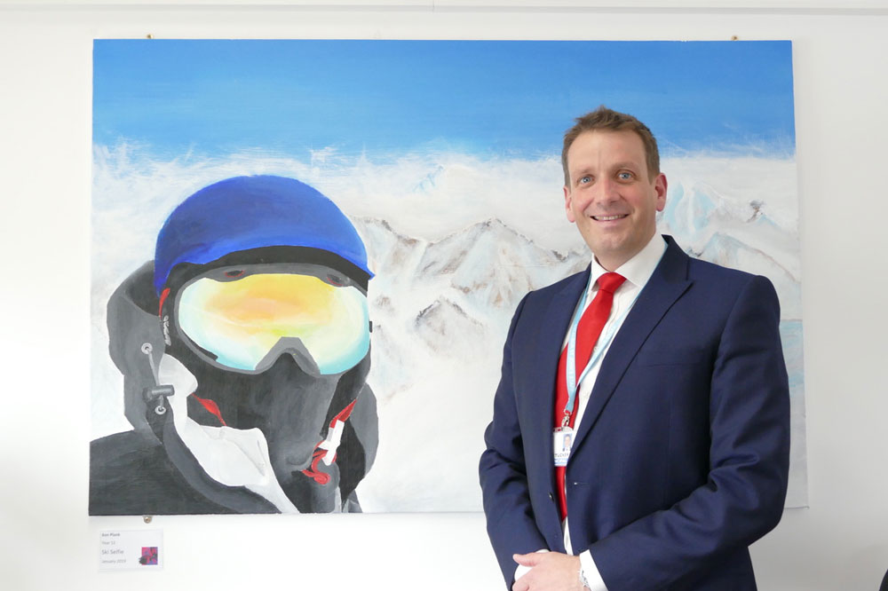 Ian Tucker, St Johns Principal in front of 'Ski Selfie' a painting by Ben Plank in Year 11