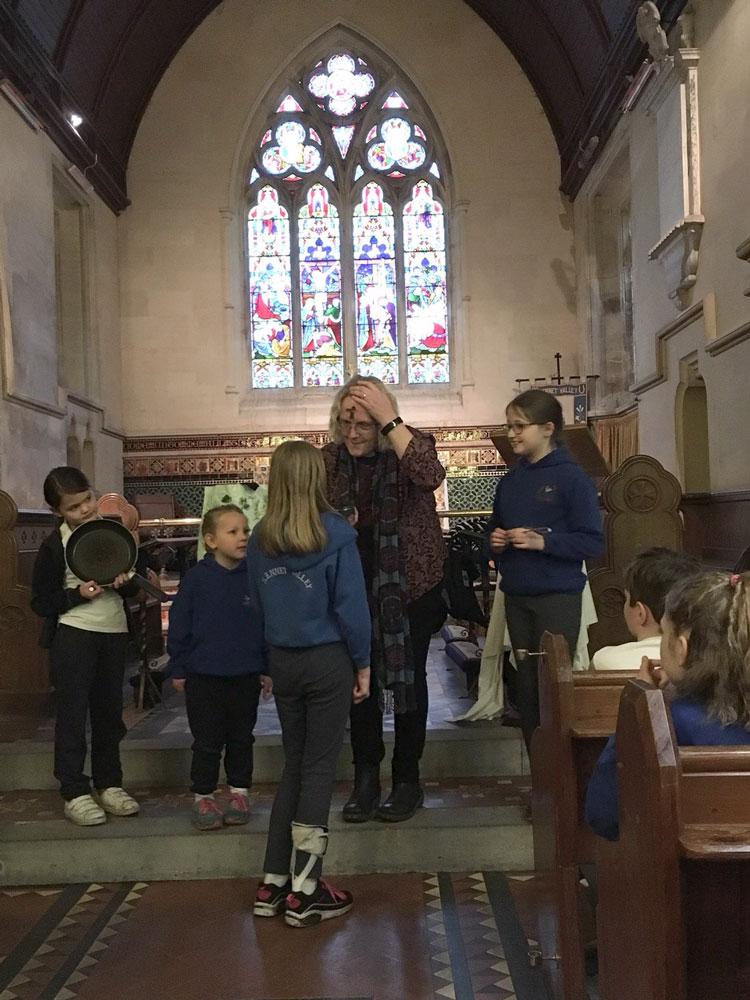 Pupils mark the Ash Wednesday ash cross on Rev. Maria Shepherdson's forehead