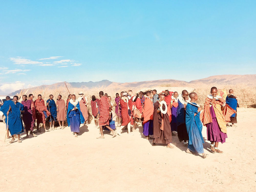 A Maasai community dancing and singing within the Great Rift Valley.  Michaela in hat and sunglasses