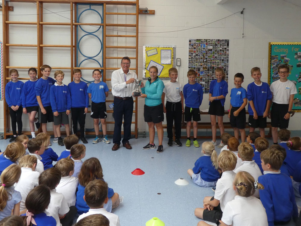 Steve Boocock (CEO of Wiltshire and Swindon Sport) presents the trophy to Kirsty Miles and Year 6 Sports Leaders