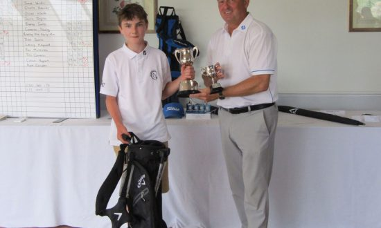 Finn Mulvey accepting the Marlborough Junior Open trophy from Simon Amor