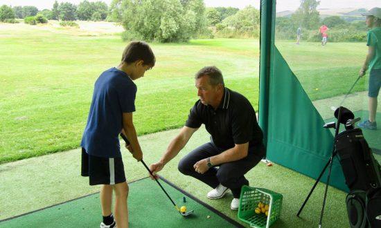 Marlborough Golf Club's professional coach Simon Amor instructs nine year old Ralph Hayward