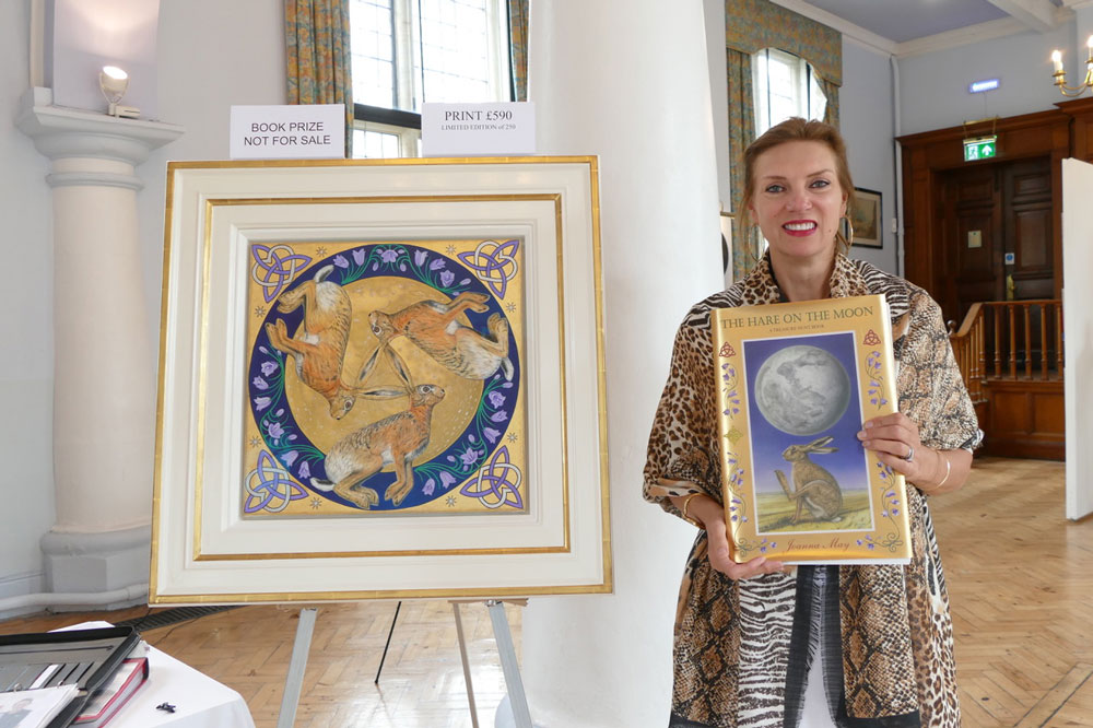 Joanna May with her book 'The Hare on the Moon' and her painting which is the prize
