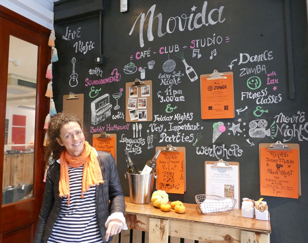 Lau Costantini in front of the board showing everything that Movida has to offer