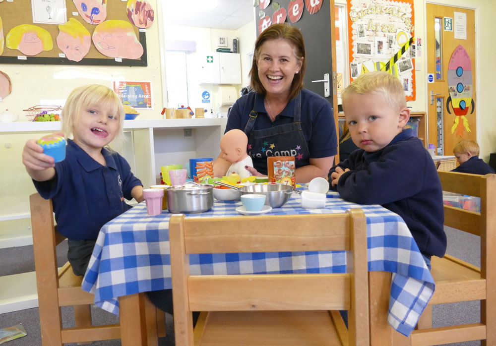 Pre School manager Vicky Camp takes tea with two pre schoolers