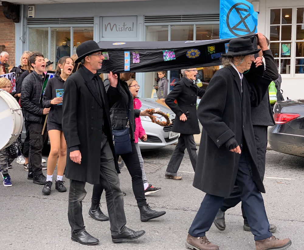 A symbolic coffin representing the Earth being carried along Marlborough High Street last Saturday