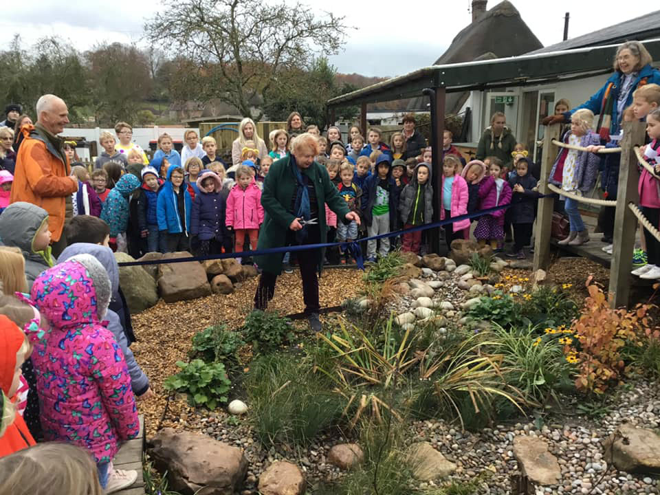 Head of Aldbourne Parish Council Alison Edmonds cuts the ribbon to declare St Michael's School Rain Garden open