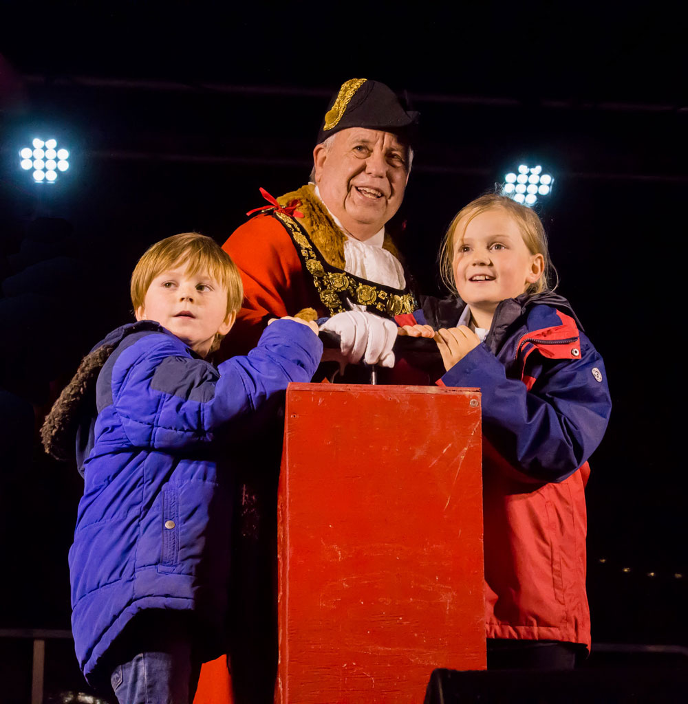 Genevieve (r) and Ted, with Grandad Mayor Mervyn Hall watch as Marlborough's Christmas illuminations burst into life all the way down the High Street