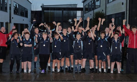 A cheering St John's Academy Year 9 rugby team, flanked by their supporting Marlborough RFC coaches, proudly show off their medals and the Swindon Schools Rugby Cup