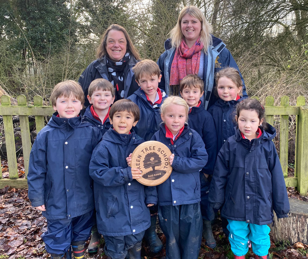 St Francis School pupils holding the Woodland Trust 'Gold Award' wooden plaque with Mrs Ashman and Miss Couse at the entrance to the school's Kindling Forest School