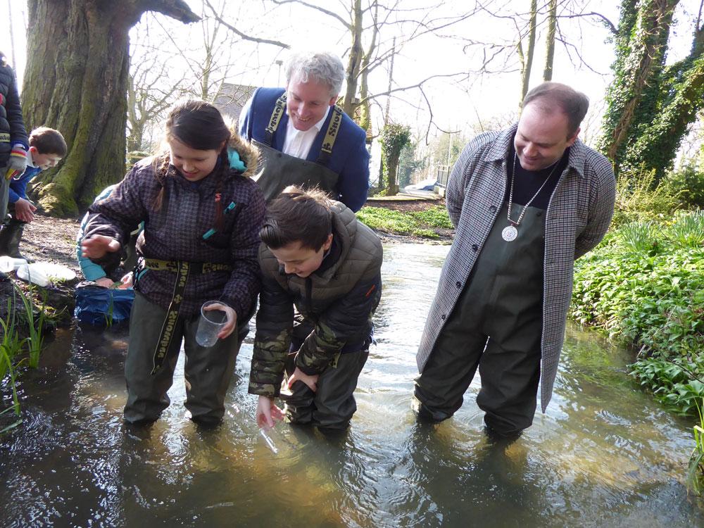 Danny Kruger MP and Deputy Mayor Mark Cooper join Ogbourne pupils releasing trout into the Kennet