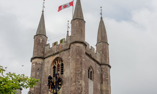 Removing the Clock Face from st Peter's Church Marlborough with the National Flag of Canada flying in honour of Canada Day 2021