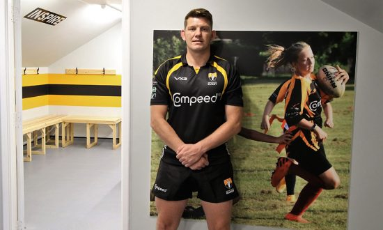 Marlborough Skipper Ben Fulton (wearing 1st XV kit) stood next to a photo of his daughter who is in the mixed age girls team